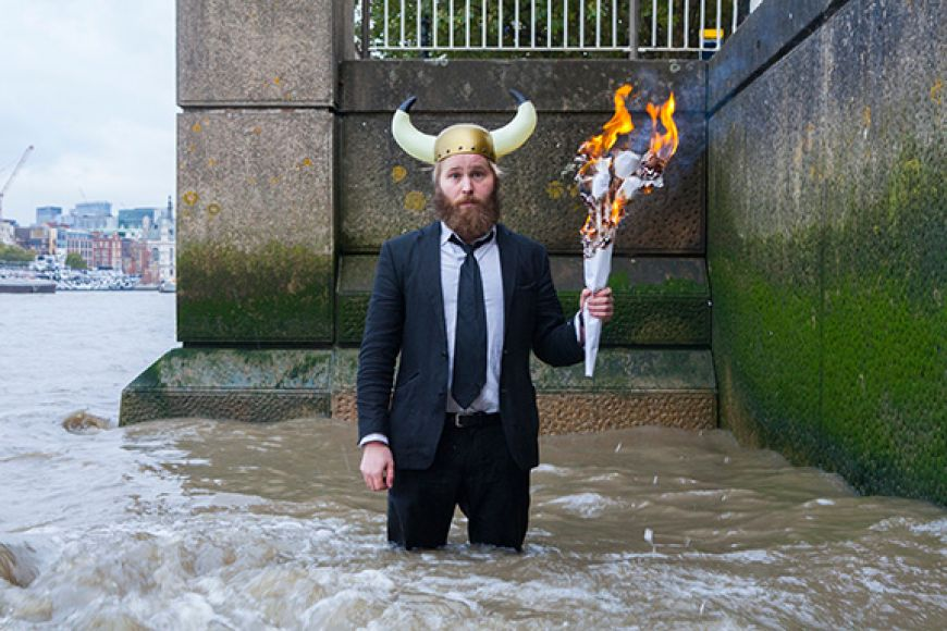 James Rowland, dressed in a suit with a viking helmet on his head, stands in the river